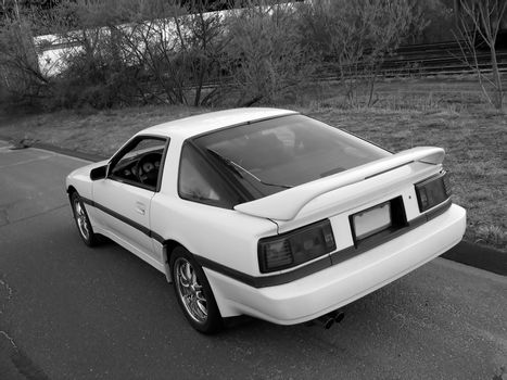 a japanese sports car captured at a cool and artistic angle, parked on the side of the street near alongside some railroad tracks - black and white