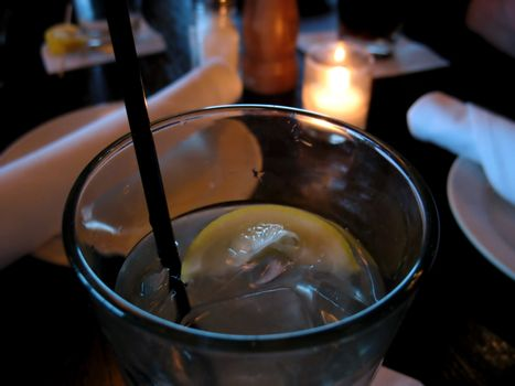 A closeup of a glass of water with lemon at a restaurant - waiting to be served.