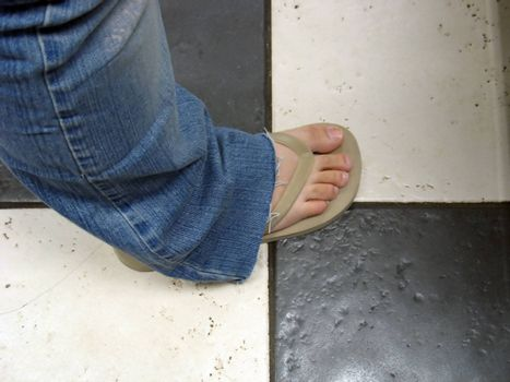 a flip flop on a girl's foot, standing on a ceramic tile floor.