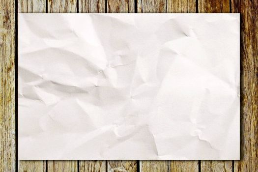 Blank crumpled white paper on wooden table