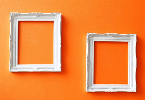 Two white vintage frames on orange wall