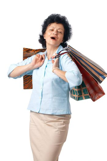 Happy elderly woman with shopping bags over white background.