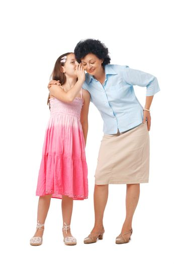 Grandmother and her grand daughter whispering something into her ear, full length.