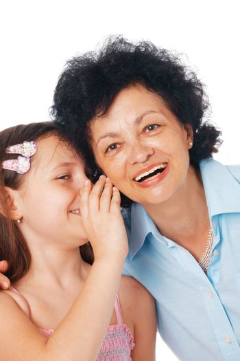 Close-up of a grandmother and her granddaughter whispering something fanny  into her ear.