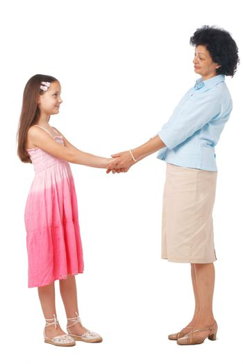 A full length portrait of grandmother holding hands with  her granddaughter.