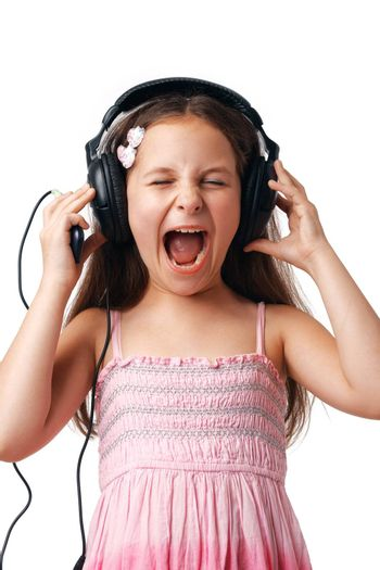 Little cute girl with headphones screaming on white background.