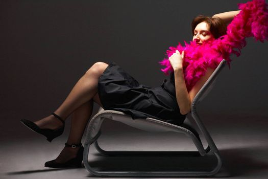 Beautiful woman in pink feathers. She's sitting on armchair