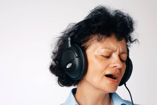 Close-up portrait of a singing elder woman with headphones.