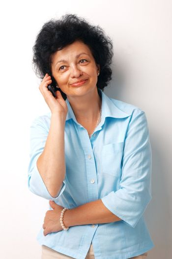 Happy senior woman using a cellphone over white background.