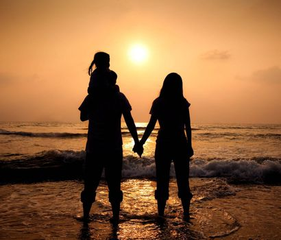 The silhouette of loving asian family walking while holding hands on beach at sunset