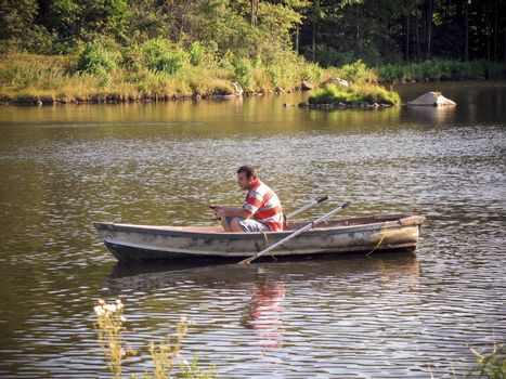 A young man fishing out of a row boat.