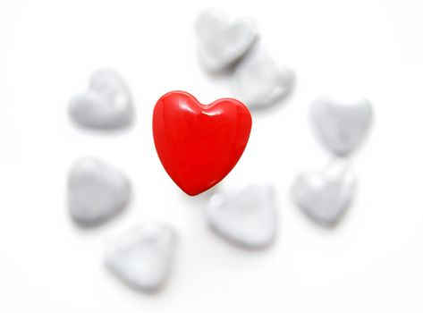 One red heart and a lot of grey. On a white background