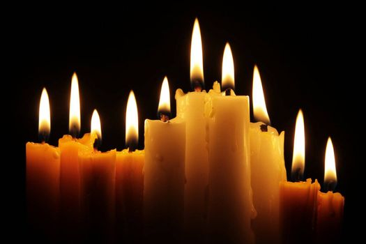 line of burning candles in the dark