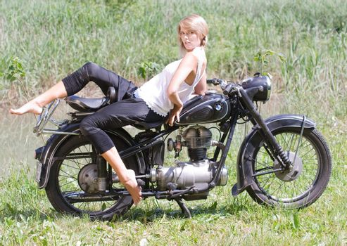 Fashionably dressed woman seated on an old motorcycle