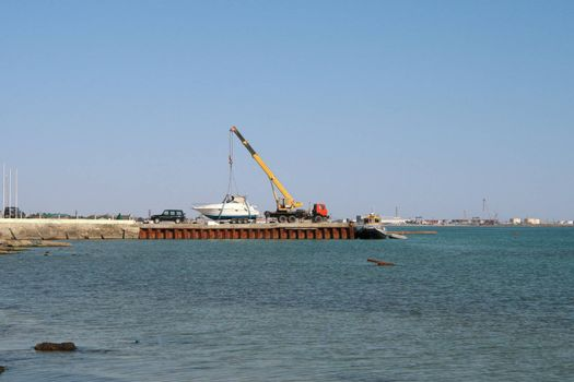Automobile crane lifts the platform for launching a boat at sea.