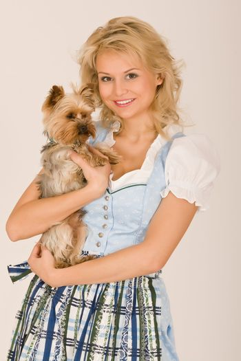 Young Bavarian girl with a dog on his arm