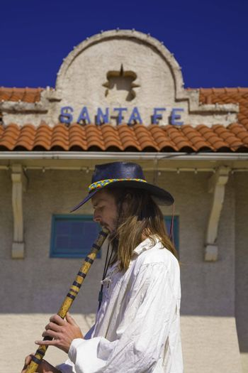 STREET MUSICIAN PLAYING A FLUTE AT SANTA FE NEW MEXICO TRAIN STATION