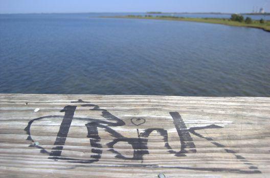 Graffiti on wood boardwalk on the ocean