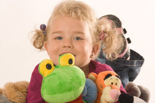 Little blonde girl with your favorite stuffed animals