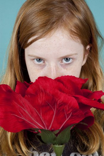 young girl is looking at you over a big red rose