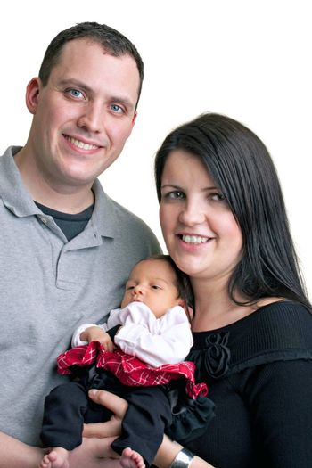 A young happy and healthy family isolated over white holding their newborn baby girl.
