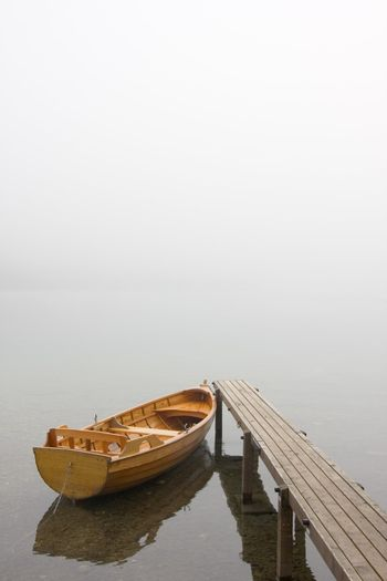 Boat at a landing stage of a lake on a misty morning