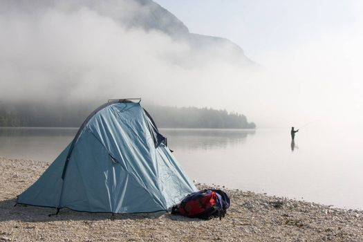 Fisherman standing in a mountain lake with his tent in the foreground