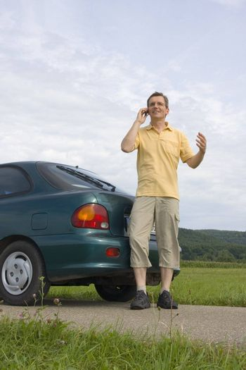 Man talking on cell phone beside his automobile