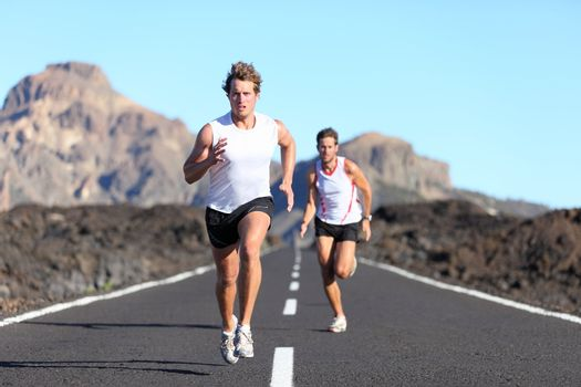 Sport running. Male Runners on road in endurance run outdoors in beautiful landscape - two men.