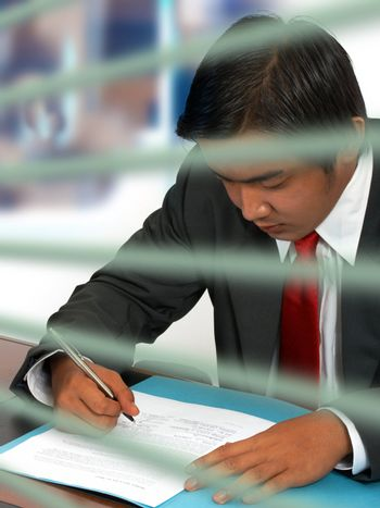 Businessman reading and signing a document