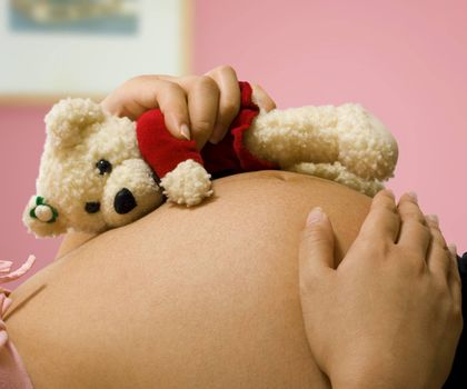 Pregnant mother lying on her bed holding a teddy bear