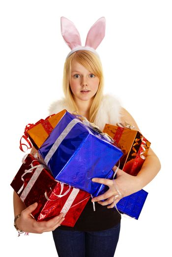 A young blonde in a bunny suit with a bunch of gifts isolated on white background