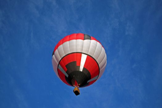 Hot air balloon on blue background with red black and white highlights.