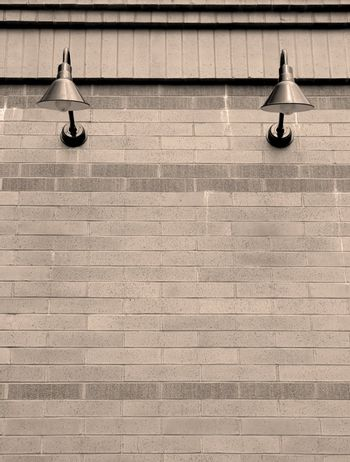 Black sconce lights on brick wall in sepia tone.