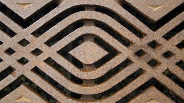 A rusty metal grate with a modern pattern.