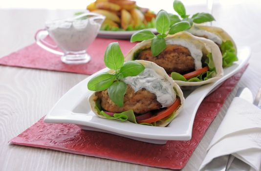 Patty in pita bread with cream sauce and vegetables