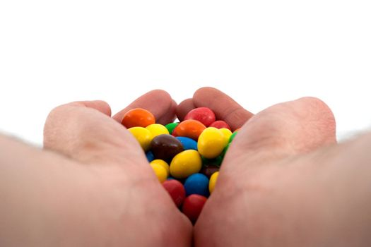 Colorful bonbons in hand on white background