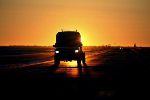 vehicle backlit by rising sun