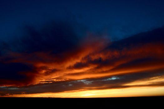 Set sun lighting up storm clouds