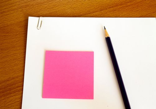 white paper with pencil and pink memo on wood table