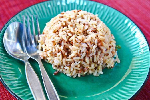 Plate of brown cooked rice from thailand