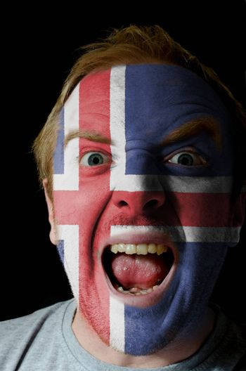 Low key portrait of an angry man whose face is painted in colors of iceland flag