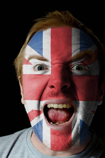 Low key portrait of an angry man whose face is painted in colors of united kingdom flag
