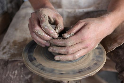 Hands of a potter. Loyalty to the traditions concept
