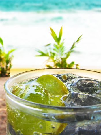 Refreshing lemon Soda With Ice At A Tropical Beach