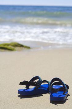 A pair of kids sandals on a tropical beach