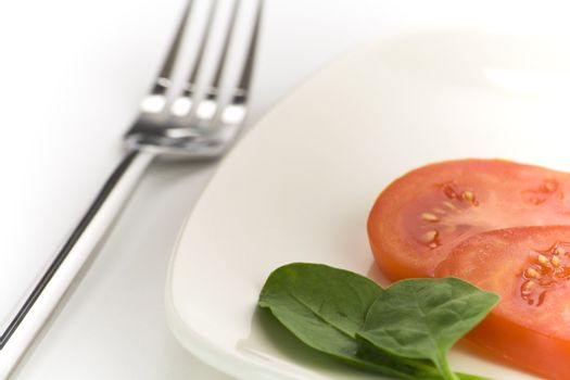 Spinach and tomato on white plate