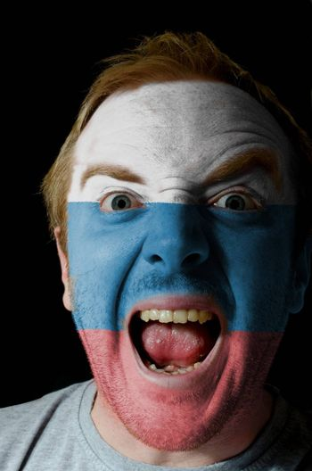 Low key portrait of an angry man whose face is painted in colors of russia flag