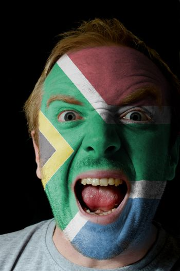 Low key portrait of an angry man whose face is painted in colors of south africa flag