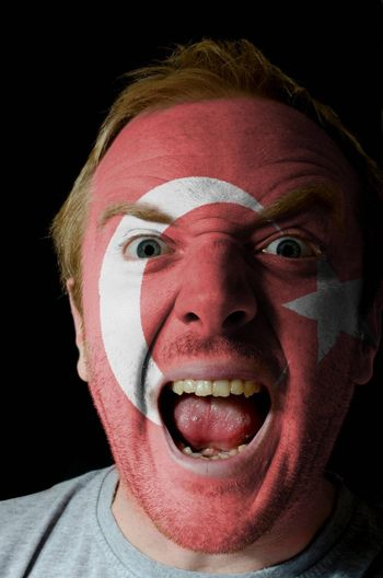 Low key portrait of an angry man whose face is painted in colors of turkey flag
